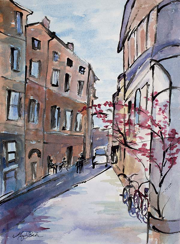 A loose watercolor and ink painting depicts a typical Italian scene with weathered brick buildings, an outdoor cafe, bikes, and cars by Mary Benke