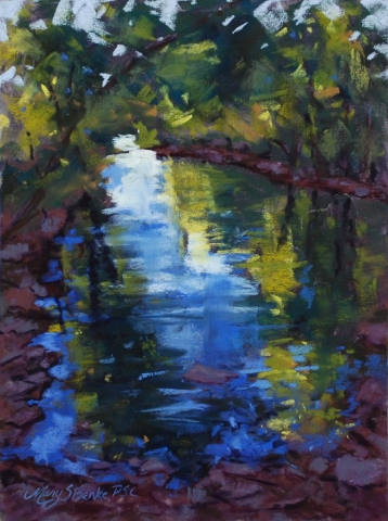 A secluded cove is sheltered by overhanging trees which allow a bit of golden light through to color the reflections in dappled blue water in this peaceful green, blue, and yellow pastel painting by Mary Benke