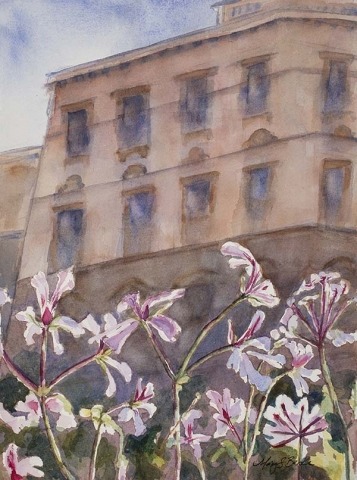 The light coming through a hotel window in Prague, a European city, features warm pinks and lavenders in the old world building with light, airy geraniums in the foreground by Mary Benke