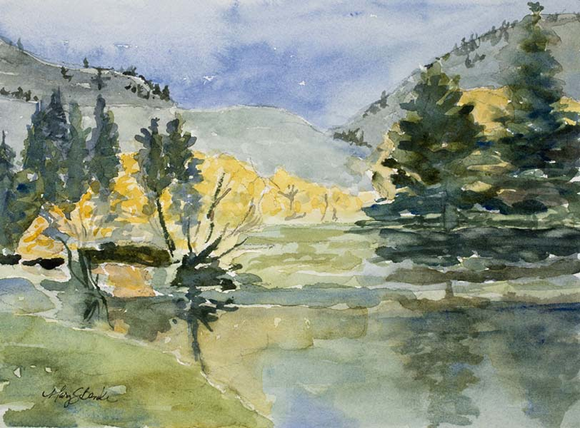 Watercolor landscape painting of yellow trees and pines reflected in a blue lake with foothills in the background by Mary Benke